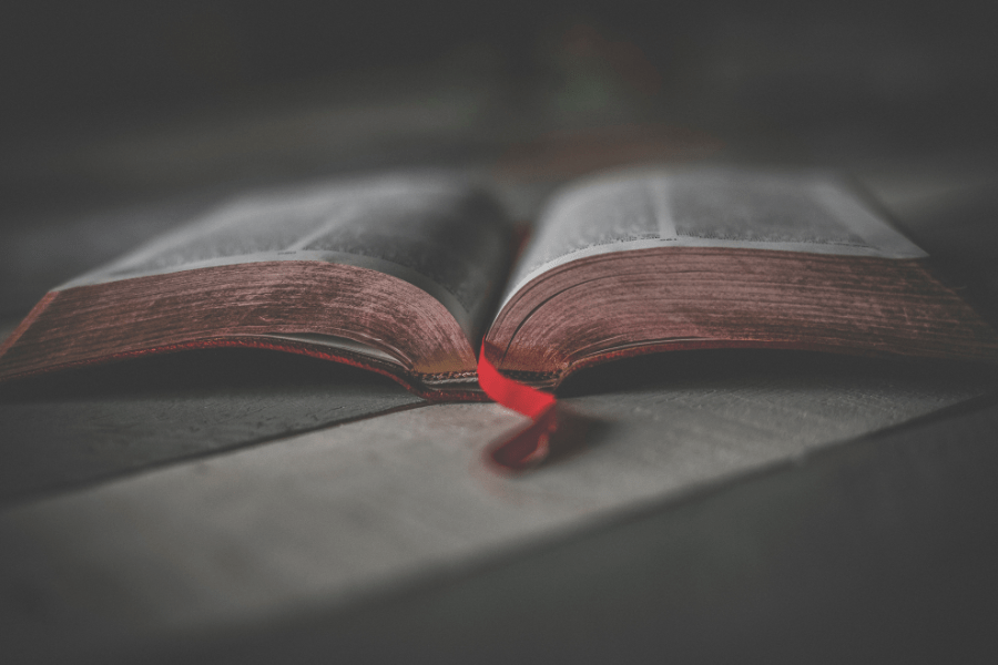 Open Bible With Red Ribbon On Table