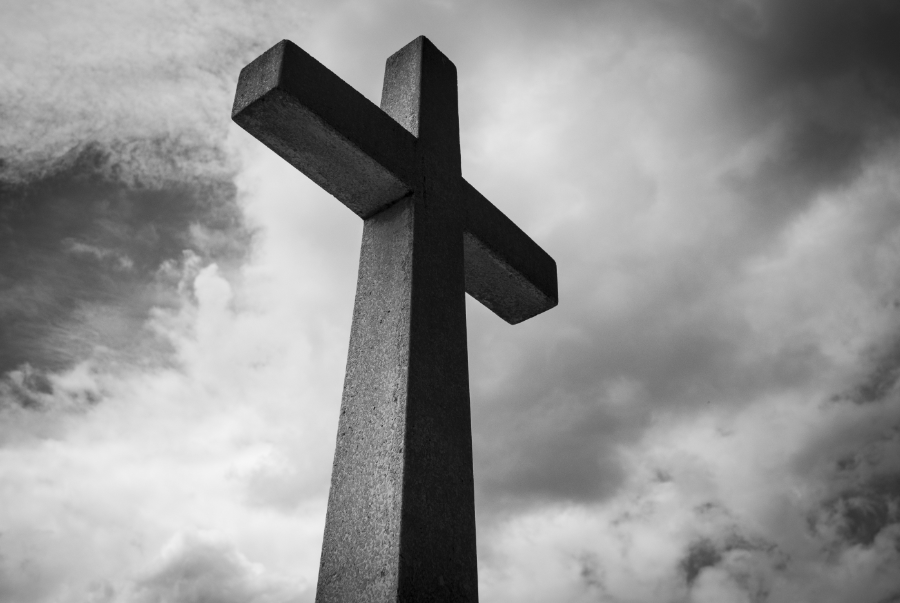 Black And White Photo Of Stone Cross With The Sky And Clouds Behind It