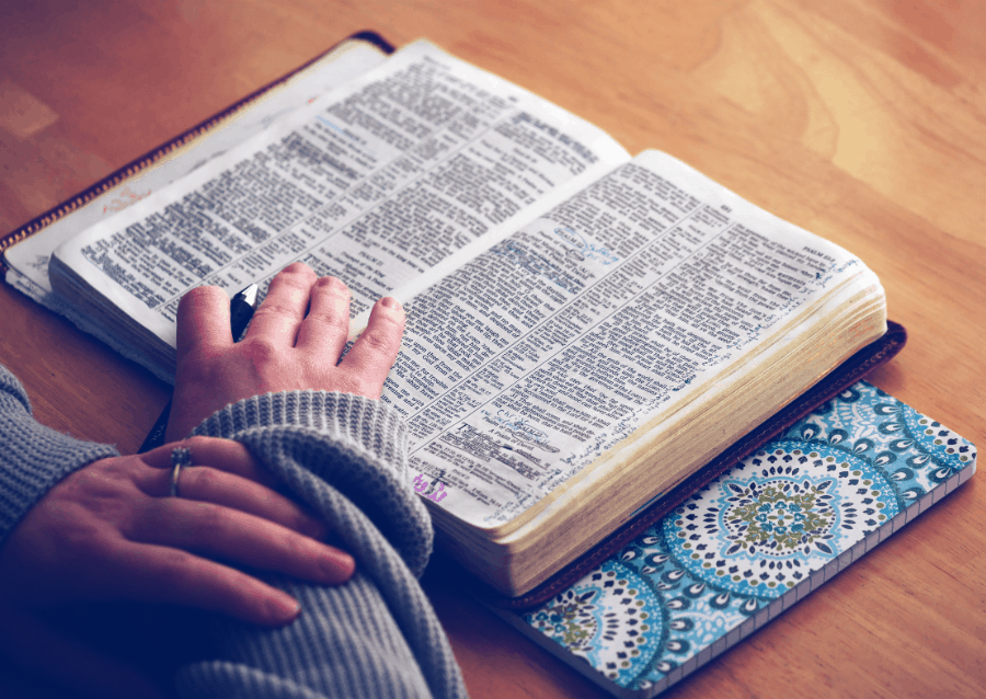 Person Reading Bible On Wooden Table With Hand On It