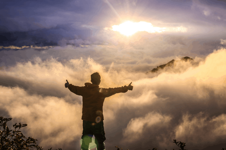 Excited Guy On Top Of Mountain With Sunlight And Clouds