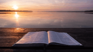 Bible On Table Near Water And Sun