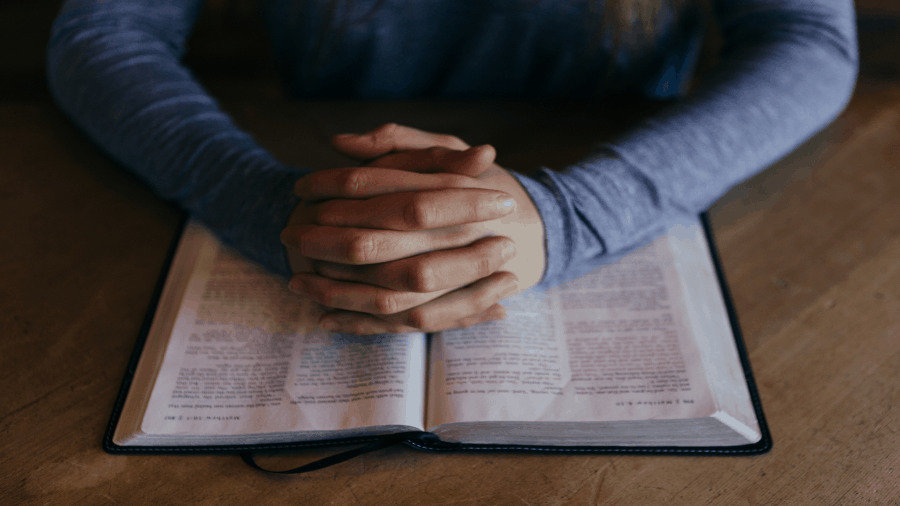 The Bible Open With Person Holding Crossed Hands On It