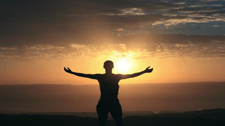 Person Standing Arms Open Towards Sun