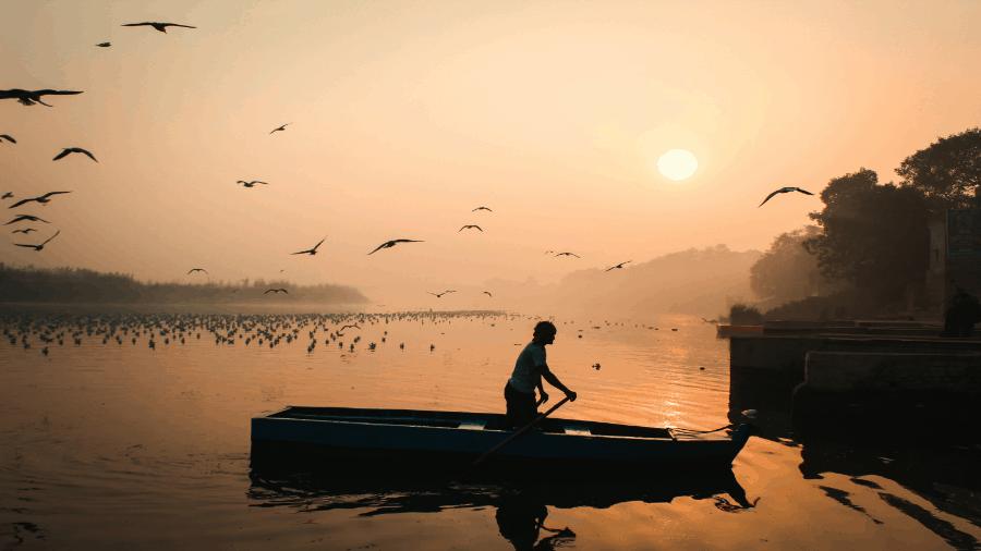Man In Wooden Boat In Lake