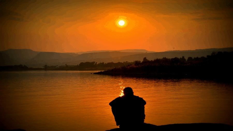 Light Shining At Dusk Or Dawn With Man At Lake 900x506
