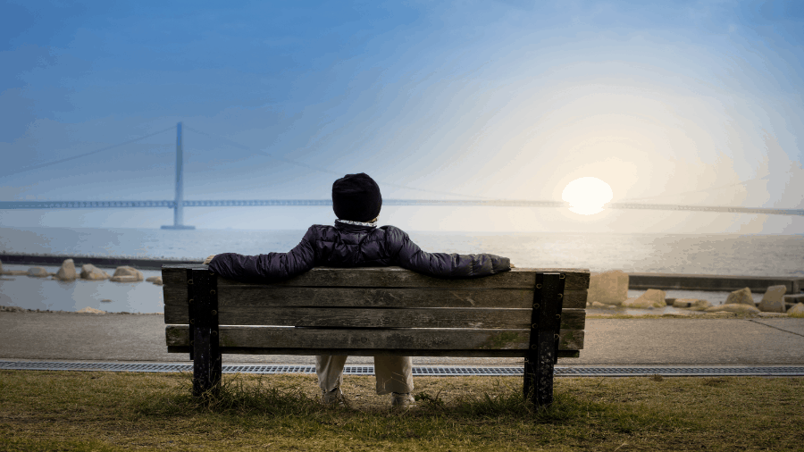 Person Resting On Bench Near Ocean 900x506
