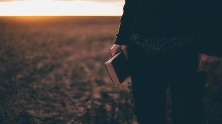 Holding Bible In Field 900x506