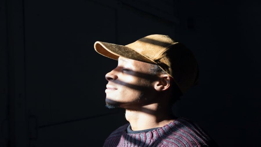 Man In Dark With Light Shinning Smiling 900x506